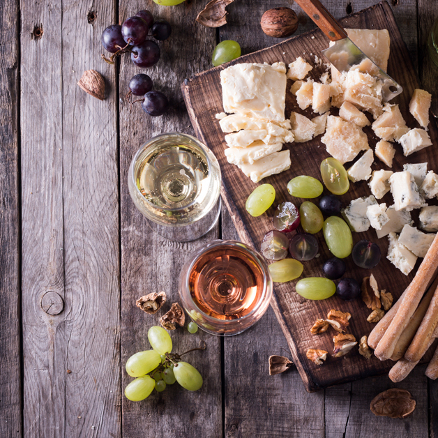 Different kinds of cheeses, wine, fruits and snacks on rustic wooden table . still life concept